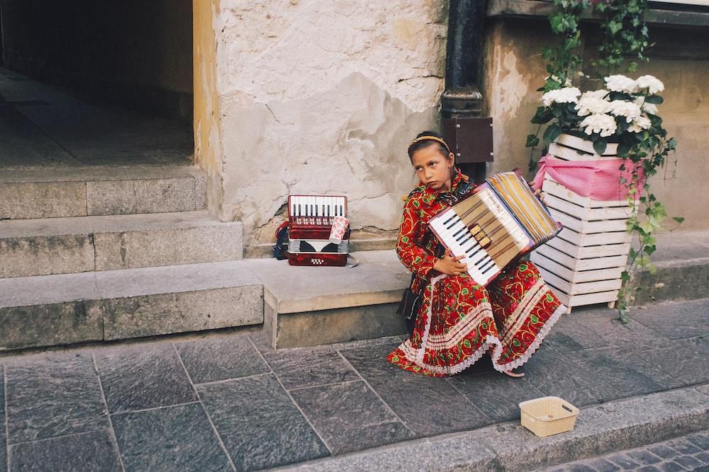 girl playing accordion in street