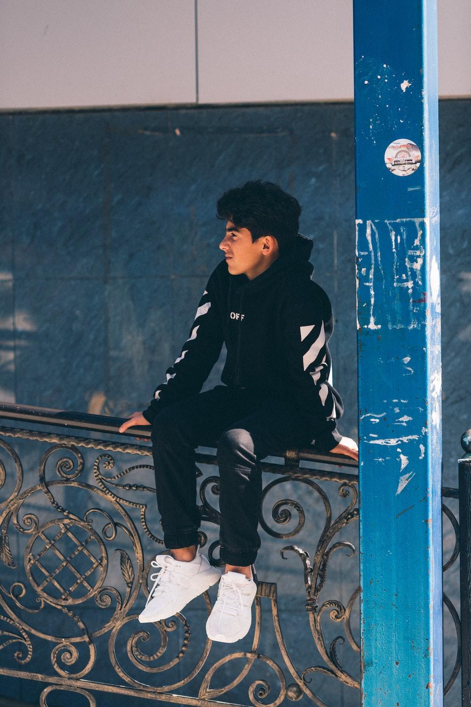 man in black hoodie sitting on metal rail