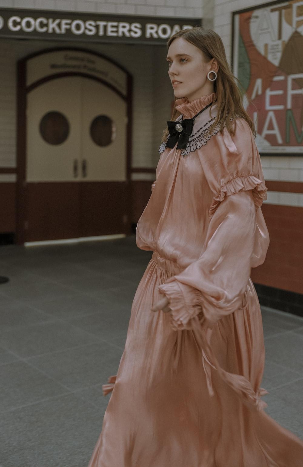 woman wearing pink long-sleeved dress across white door