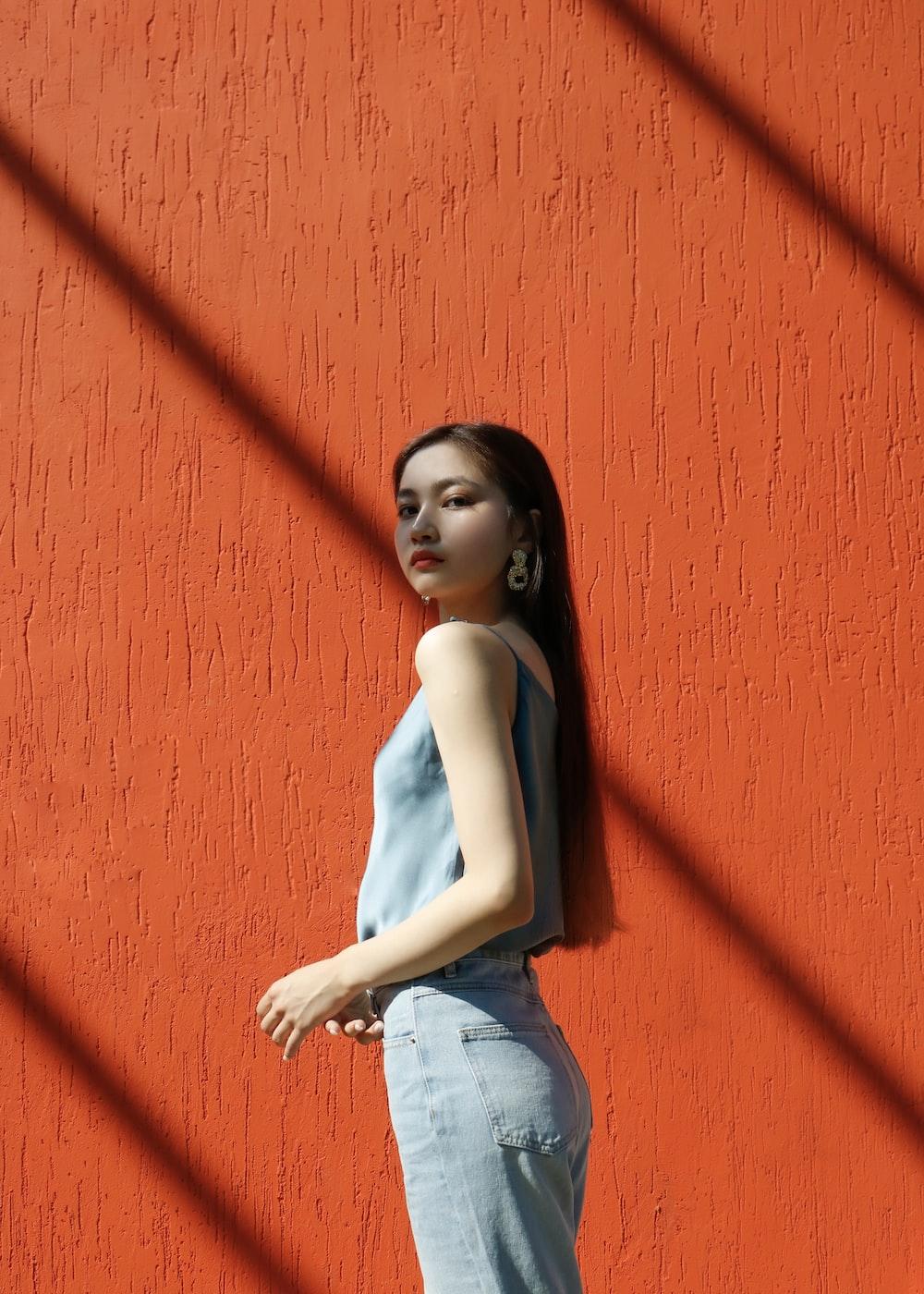 woman in blue top standing beside wall