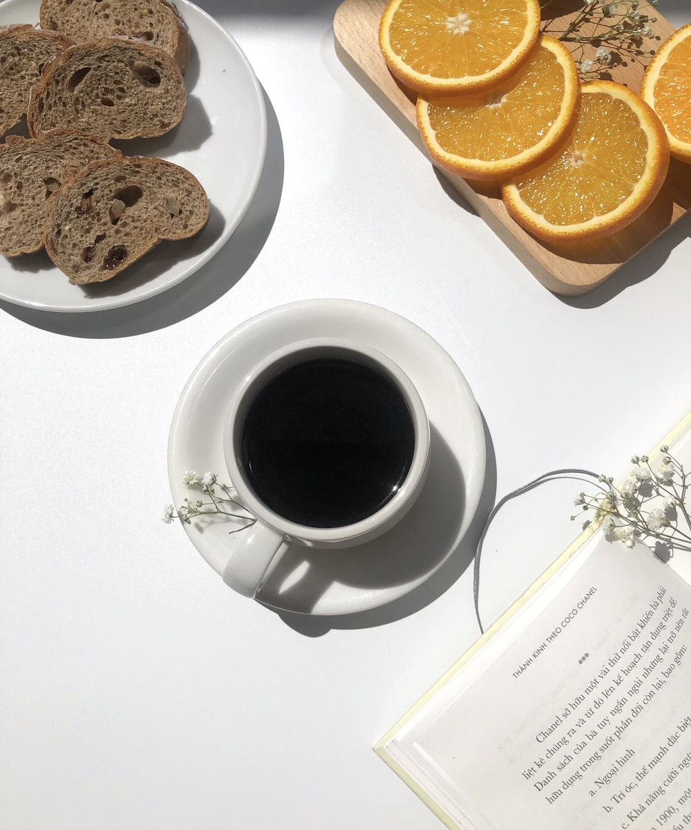 coffee in mug near breads and oranges