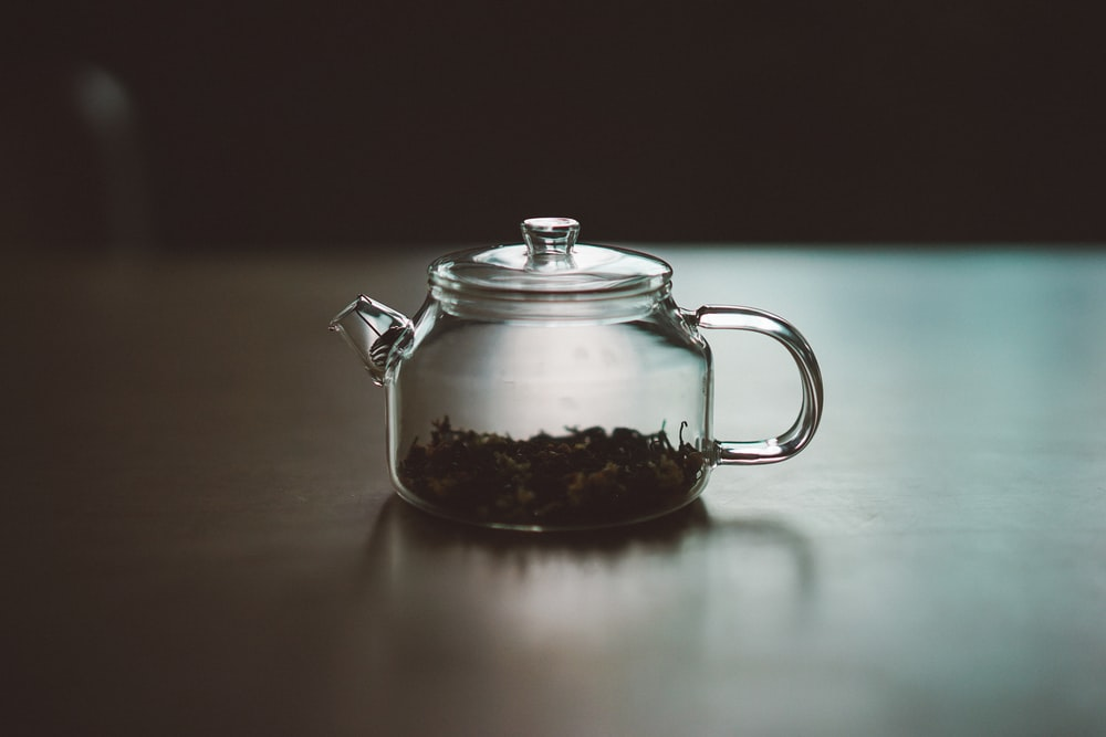clear glass teapot on wooden surface