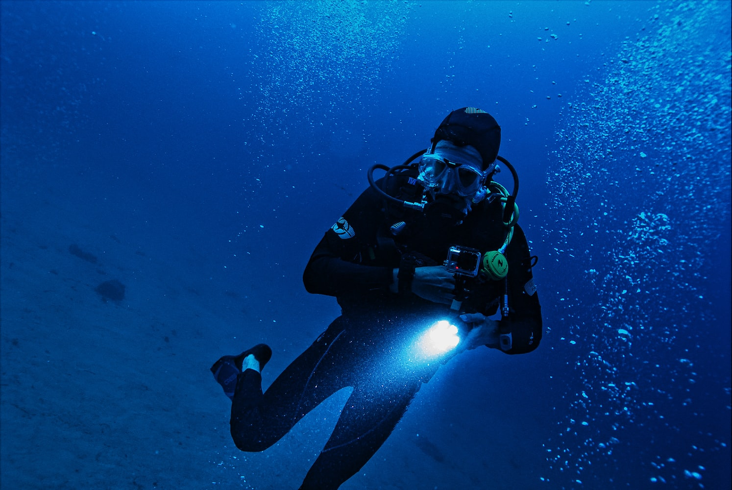 Diver holding a flashlight while swimming underwater