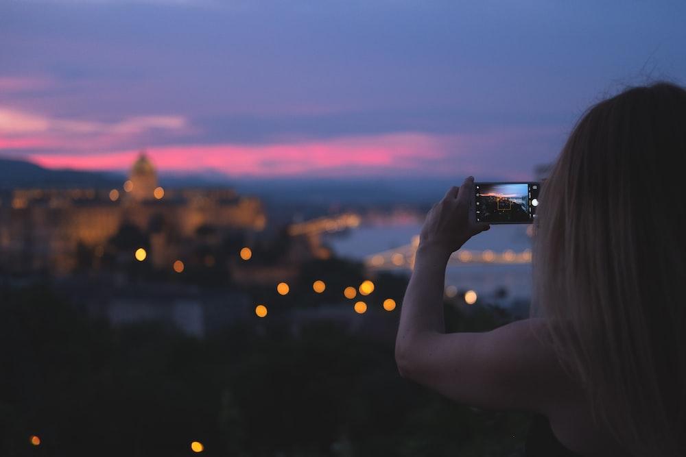 woman using smartphone taking photo
