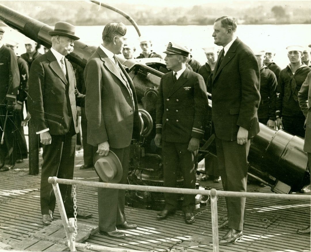 The great geophysicist Vening Meinesz on the right being wished success by Secretary of the Navy Curtis D. Wilbur on board United States Submarine S-21. Meinesz was heading an expedition to make the first marine gravity observations off North America.
