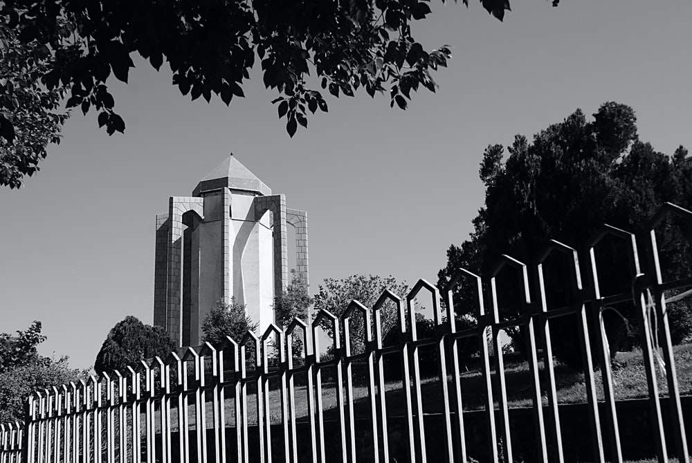 building near fenced in grayscale photo