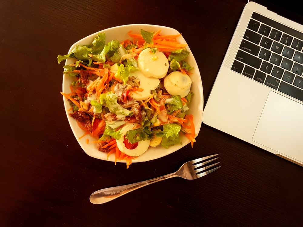 white ceramic bowl with vegetable salad beside grey laptop computer