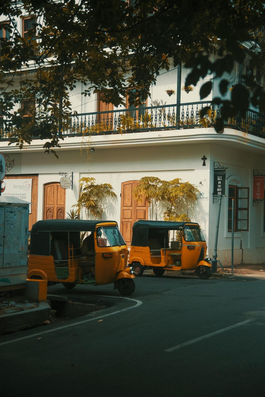 two yellow autorickshaws park near apartment