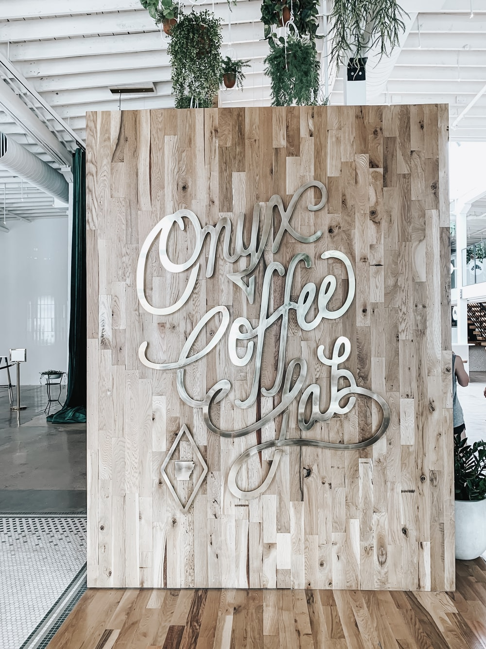 brown wooden wall board with metal letter signage inside coffee shop