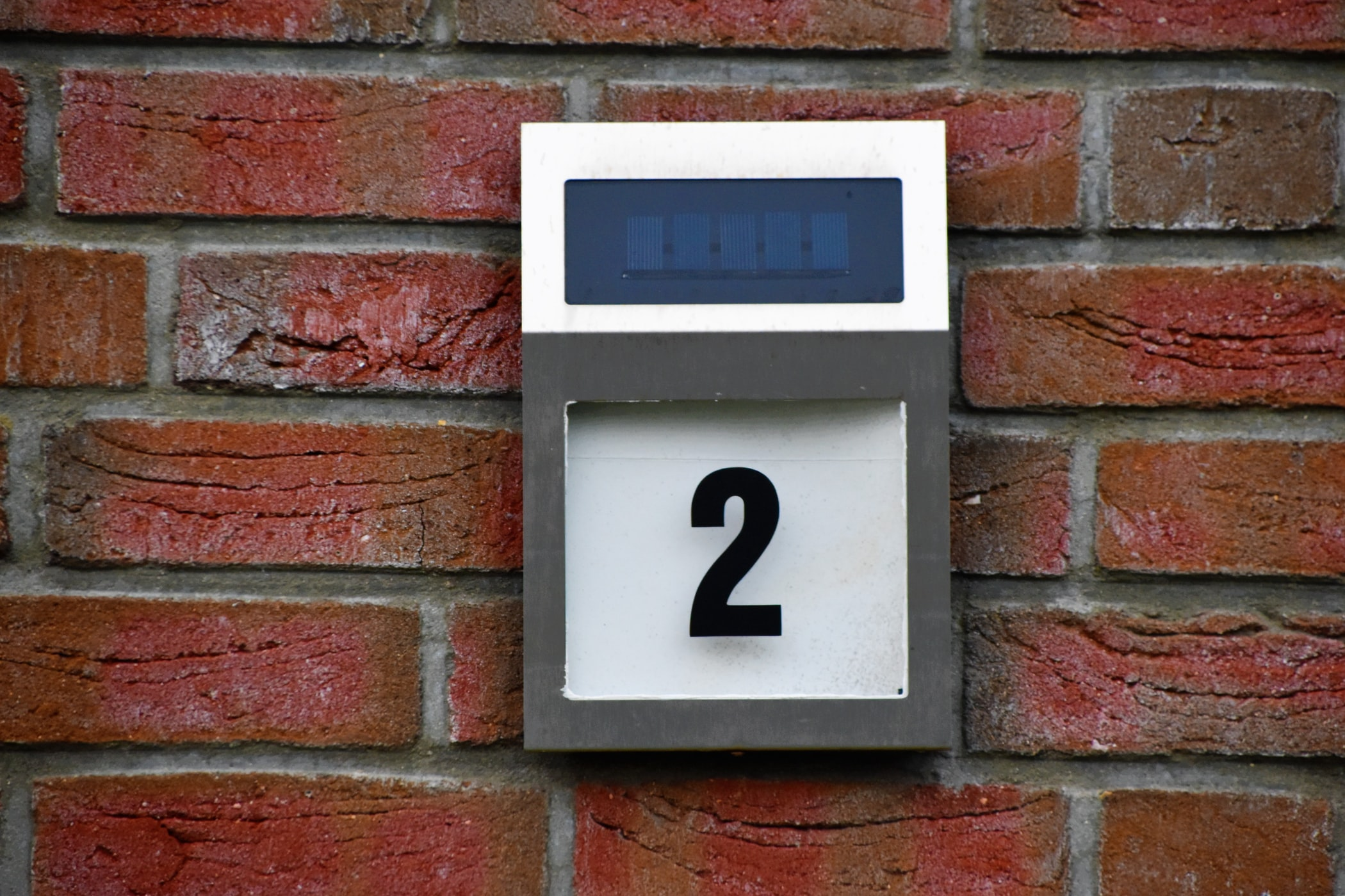 Sign showing the number 2 hung on a brick wall