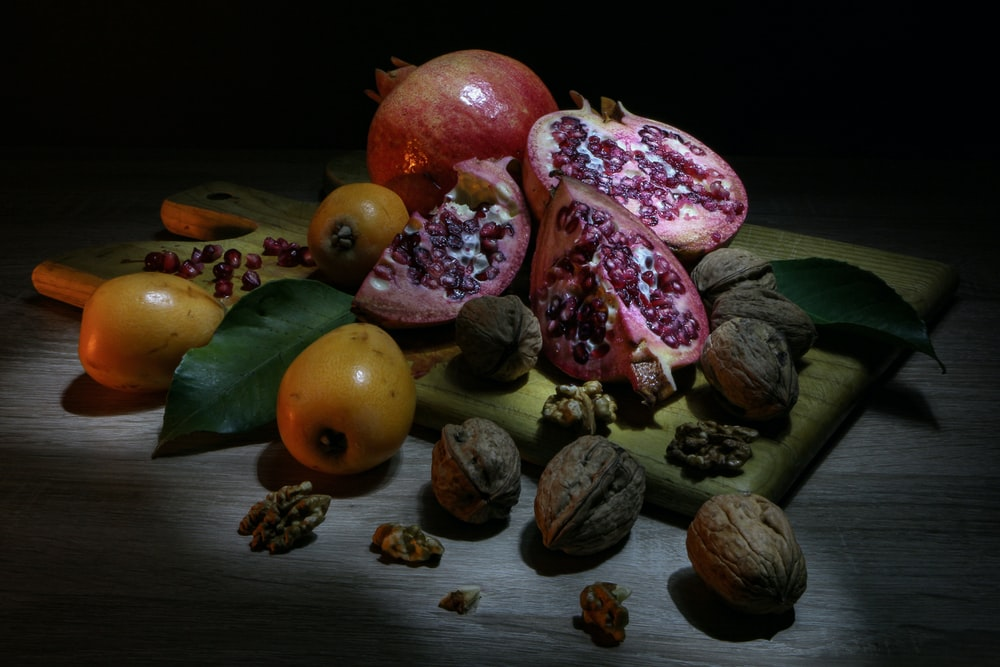 brown walnuts beside pomegranate fruit on board