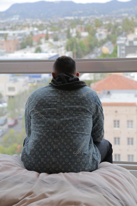 man wearing grey dress shirt sitting on bed