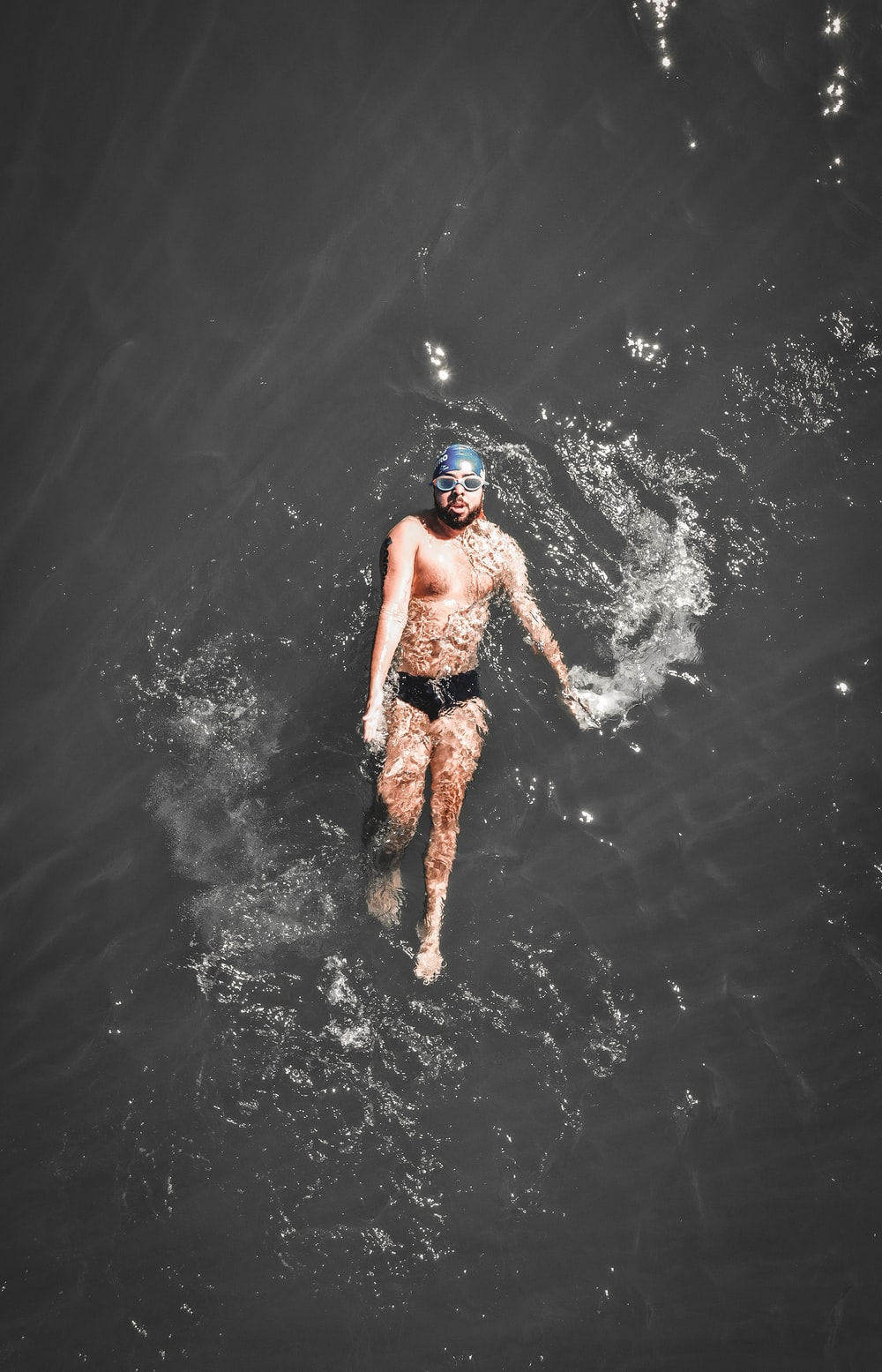aerial photography of man swimming on water