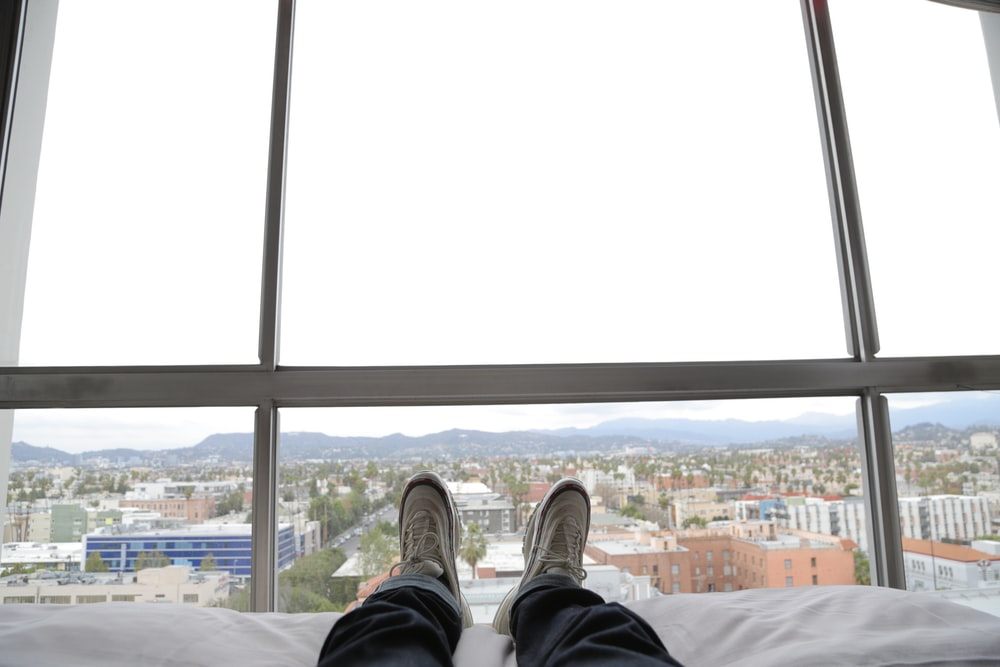 man lying on bed wearing black pants and white sneakers