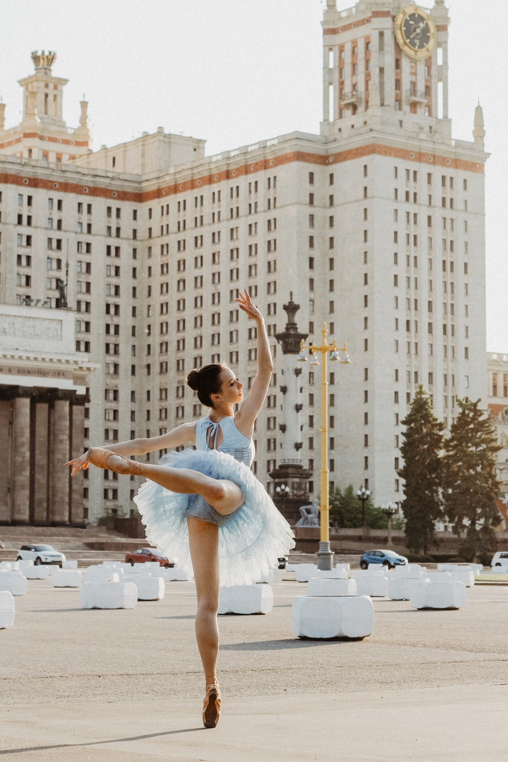 ballerina dancing near white concrete building during daytime