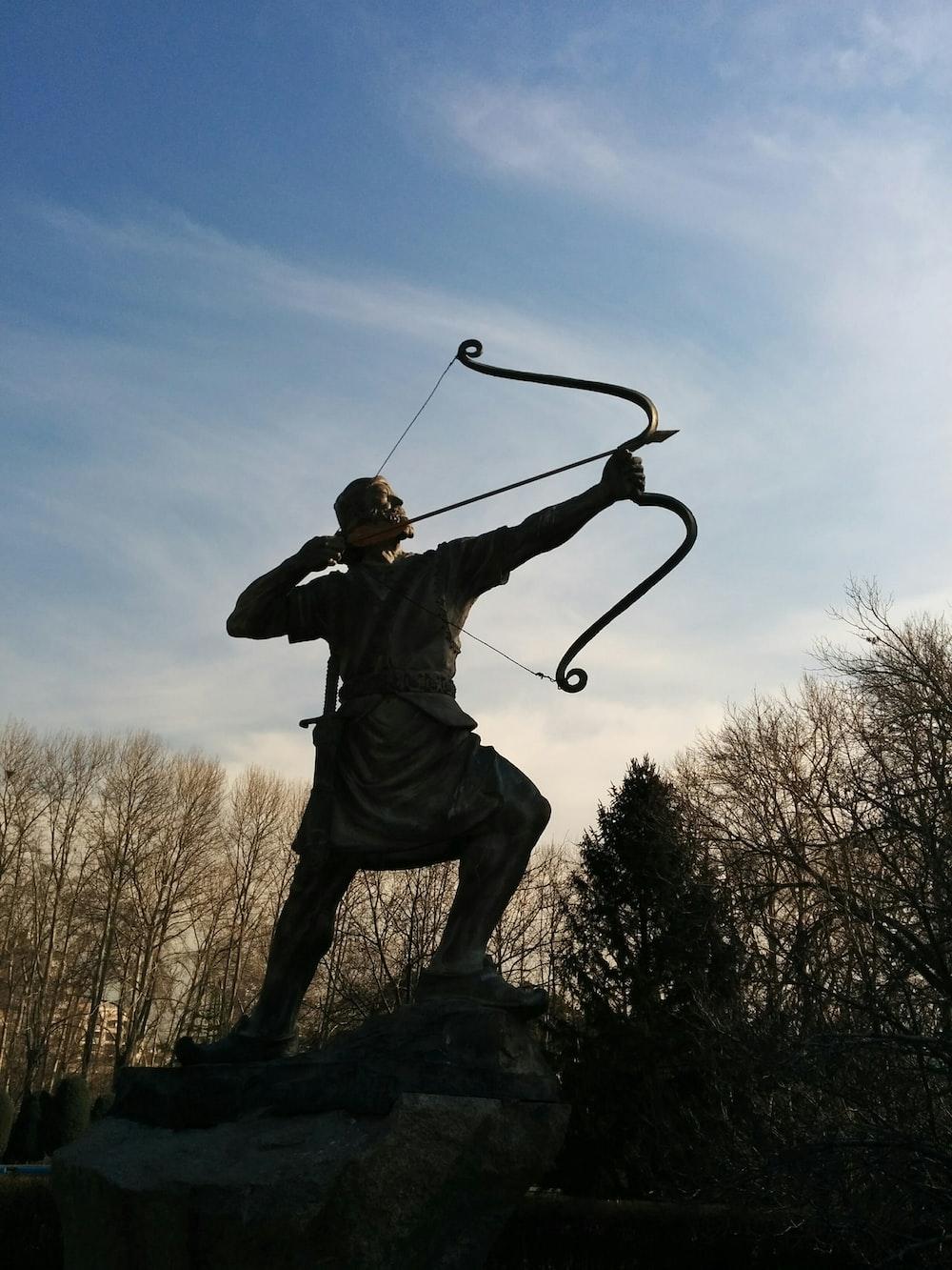 man holding archer statue