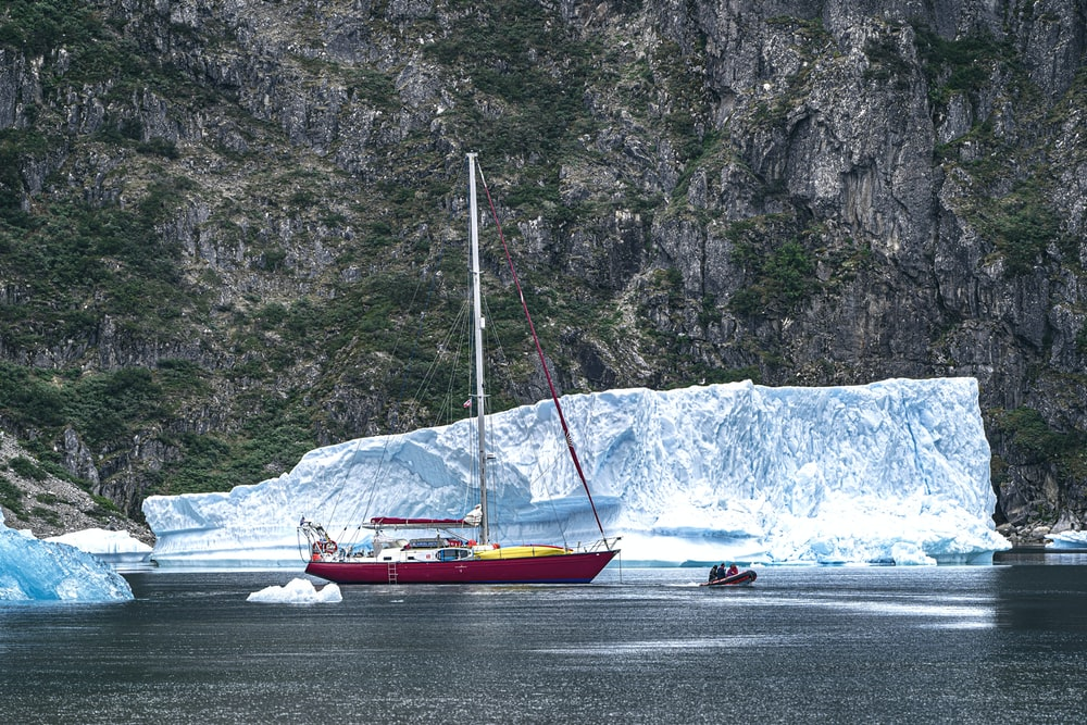 red boat on water beside ice berg