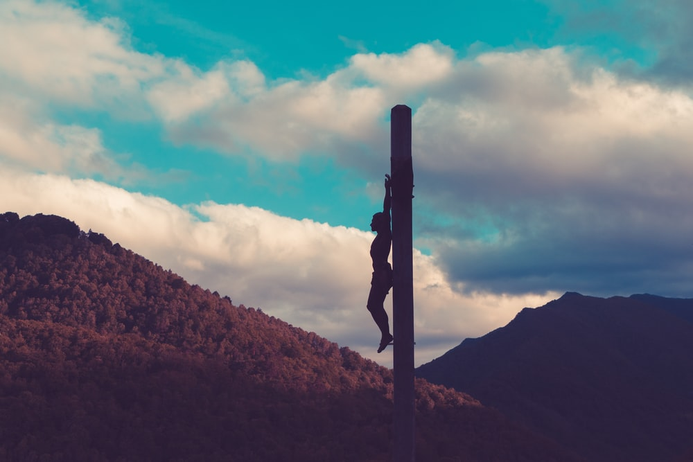 silhouette of crucified person during daytime