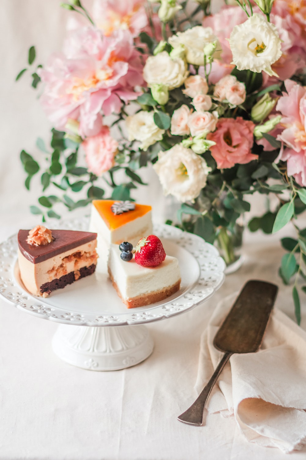 cake slices on cake stand beside cake server and flowers