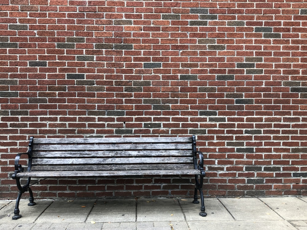 gray wooden bench beside brown wall