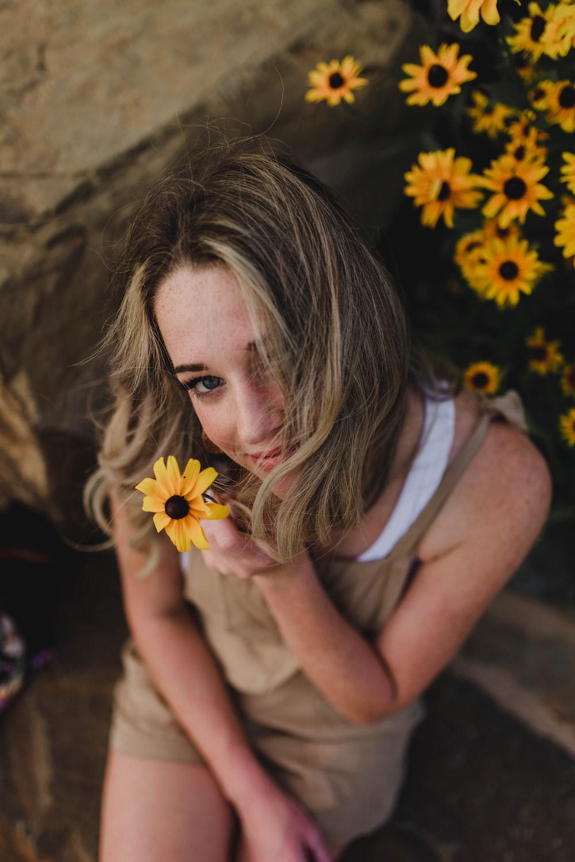 woman holding yellow sunflower