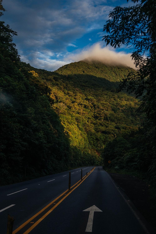 gray top road near green grass mountain