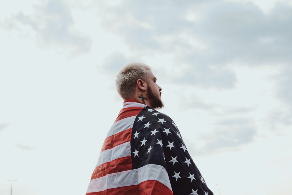 shallow focus photo of man wearing flag of USA under cloudy sky during daytime