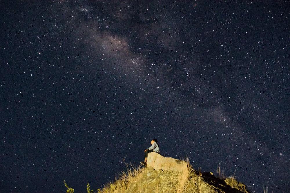 man sitting on mountain top under starry night sky