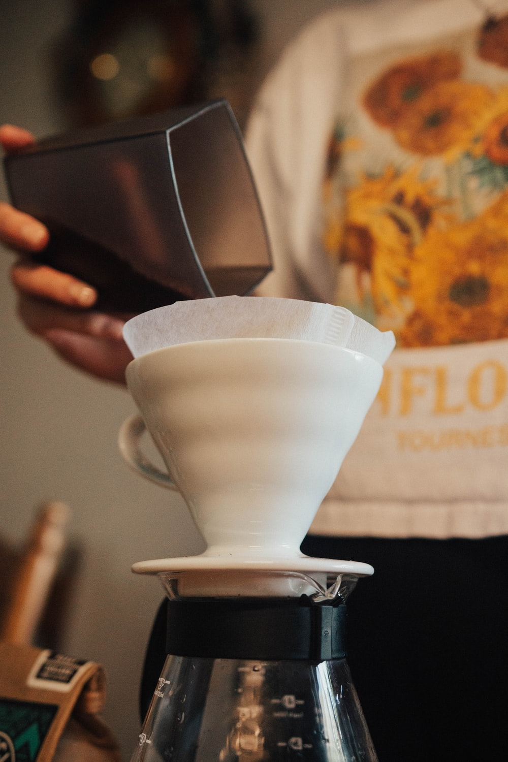 woman pouring coffee powder into cup with filter