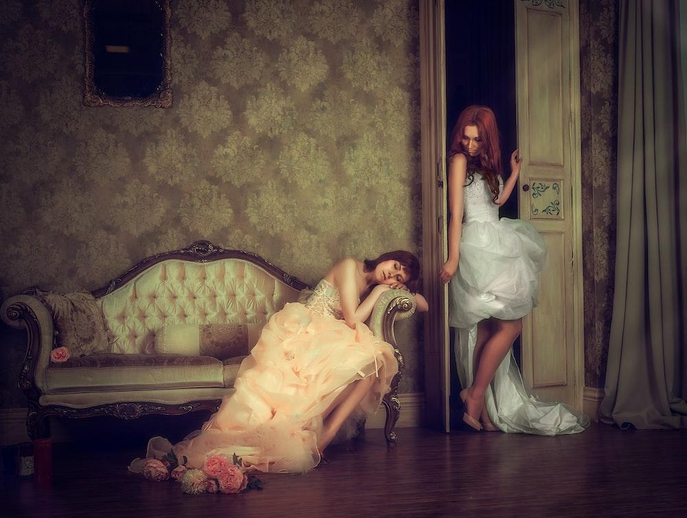 woman sleeping on sofa beside woman on door painting