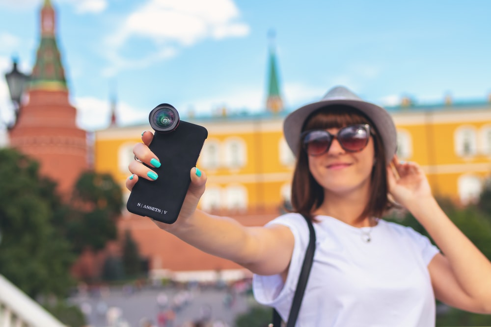 woman holding smartphone with clip lens