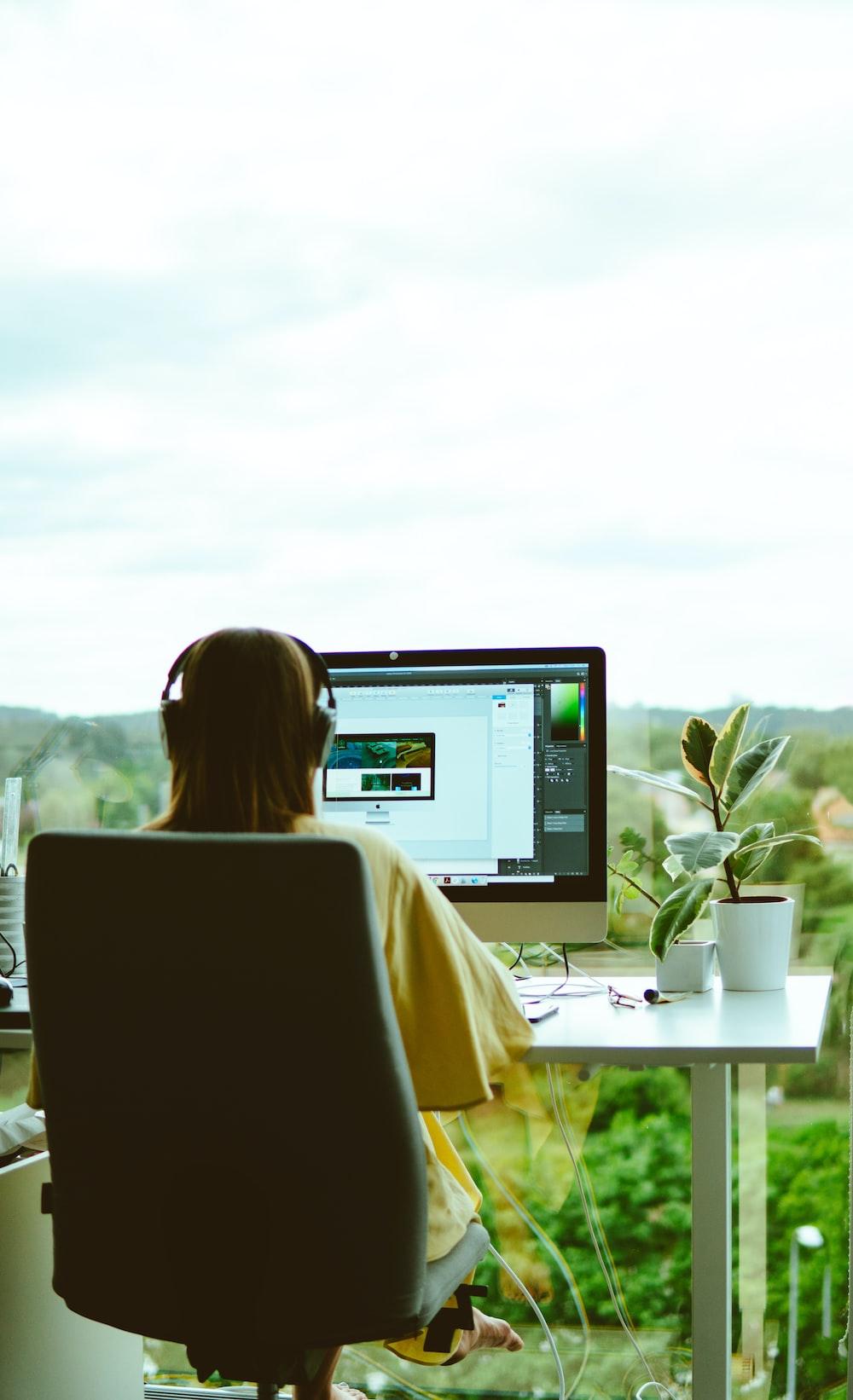 woman wearing yellow blouse using computer