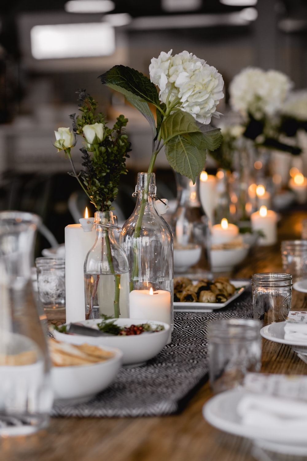 selective focus photography of white flowers beside lighted candle on table