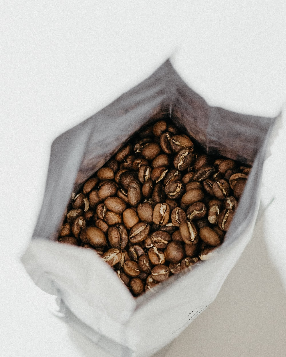 brown coffee beans inside white sack
