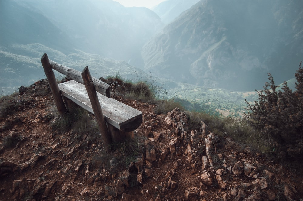 brown wooden bench on mountain