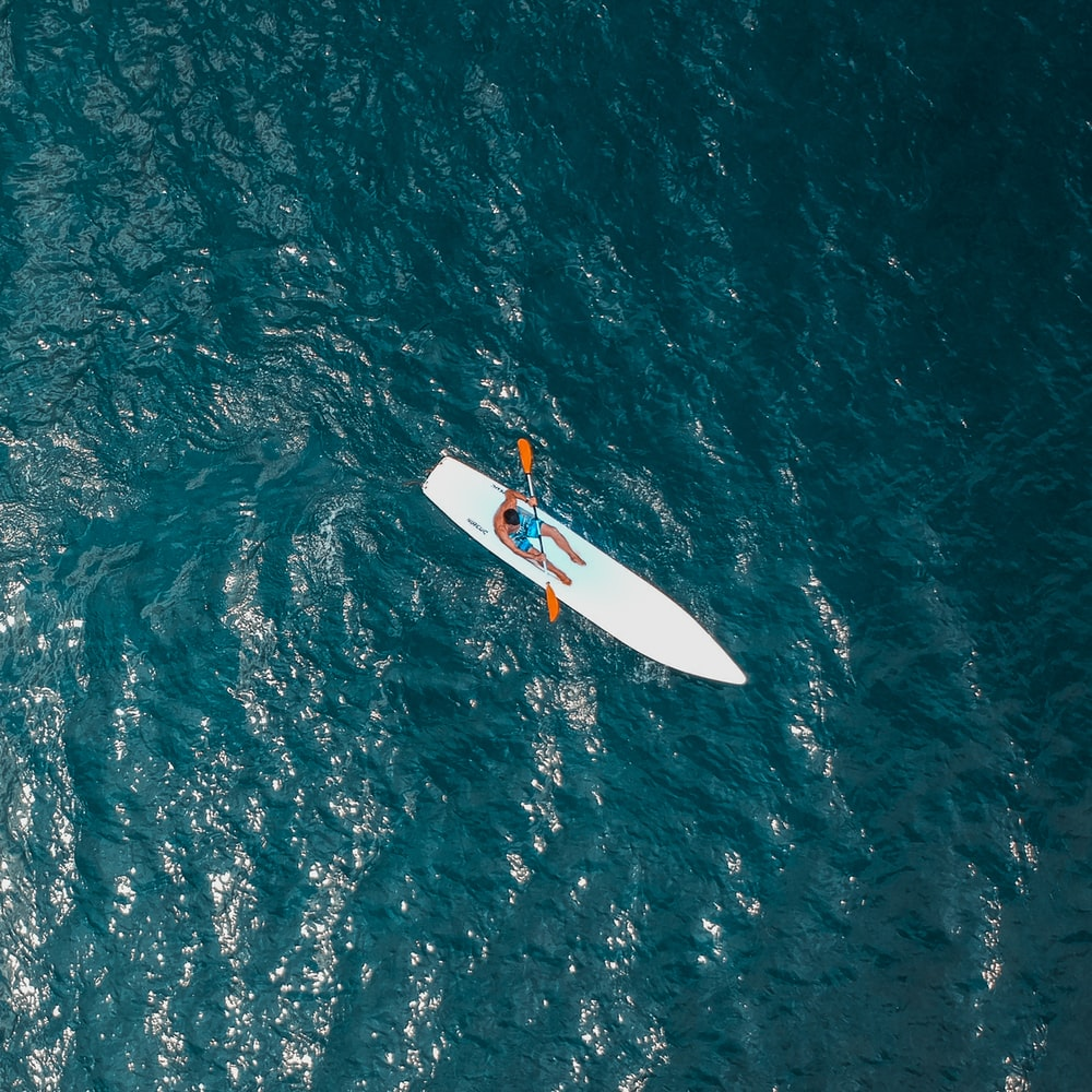 man riding white paddle boat
