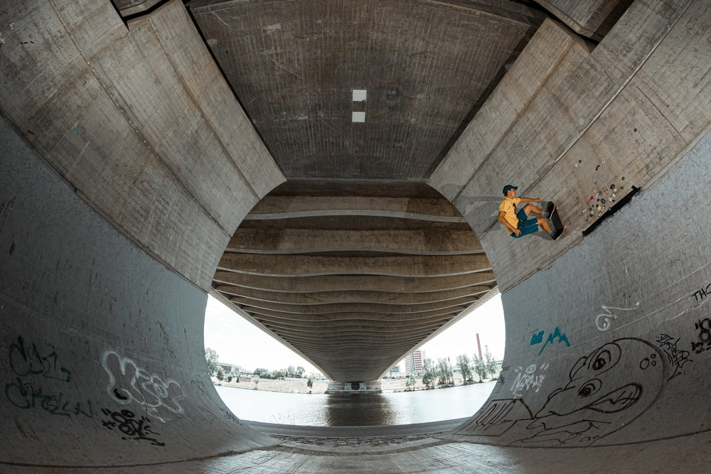 skateboarder under bridge