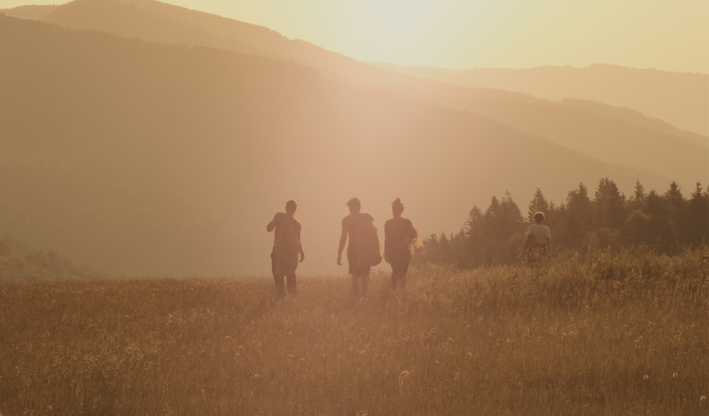 three people walking on brown fields during daytime