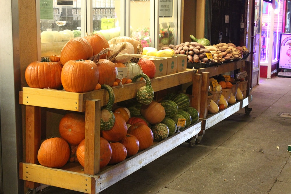 orange pumpkins on rack in front of store