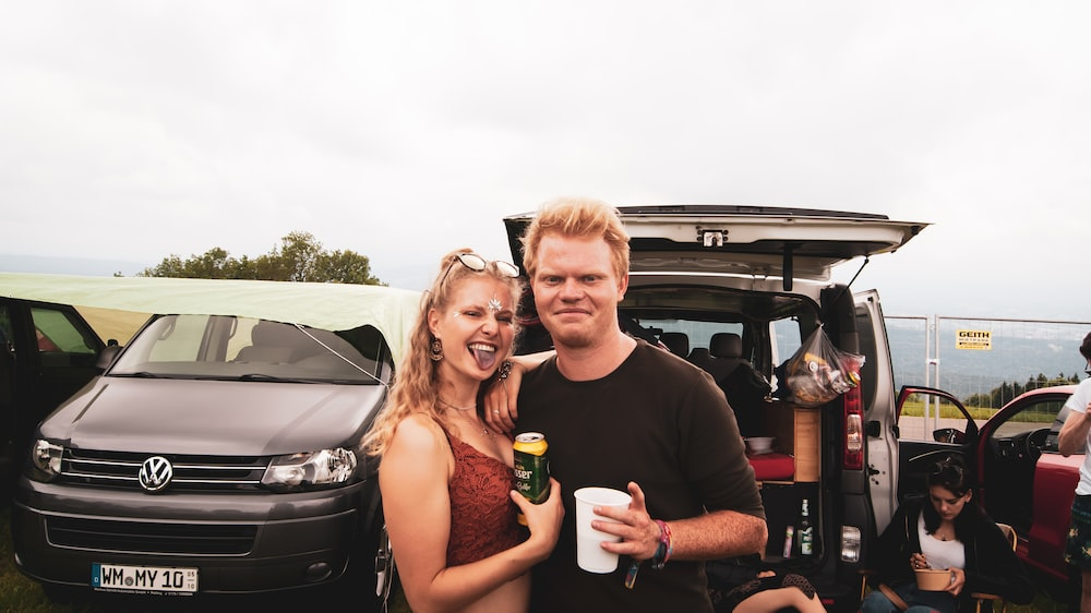 man and woman standing near vehicles