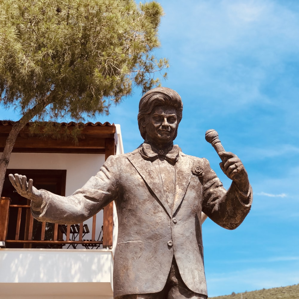 man holding microphone statue