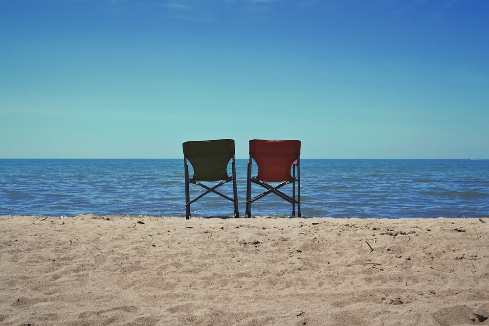two red and gray camping chairs