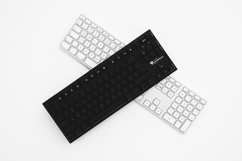 two black and white wireless keyboards