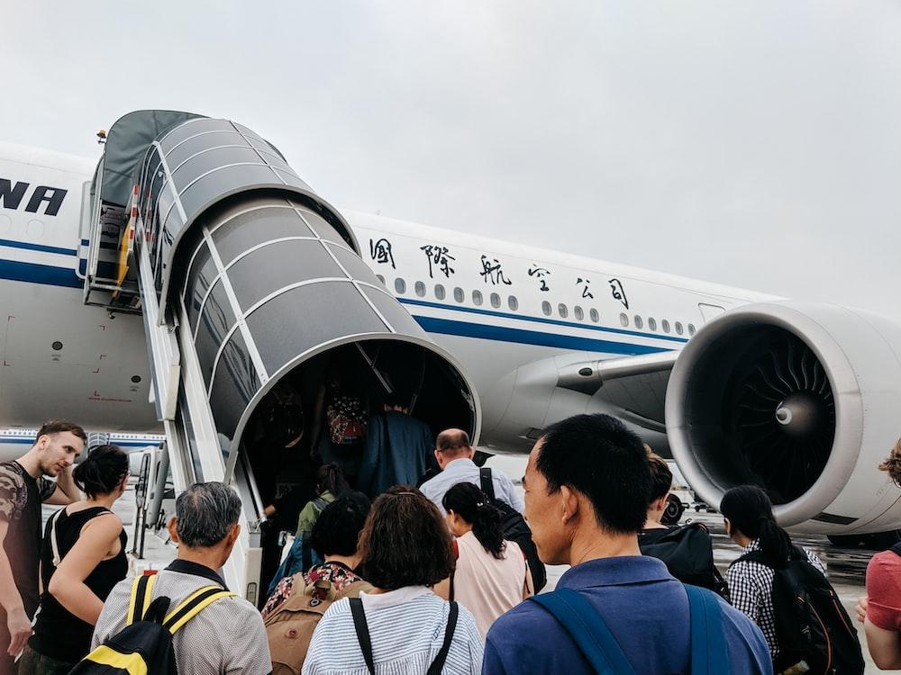 people walking towards airplane during daytime