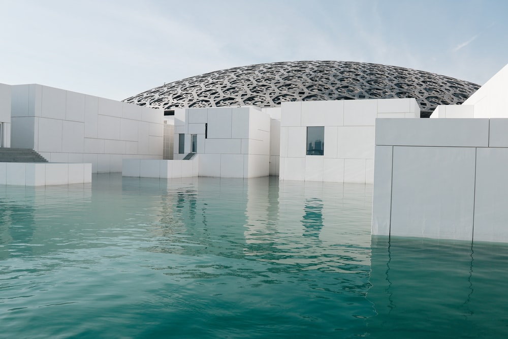 white concrete structure beside body of water