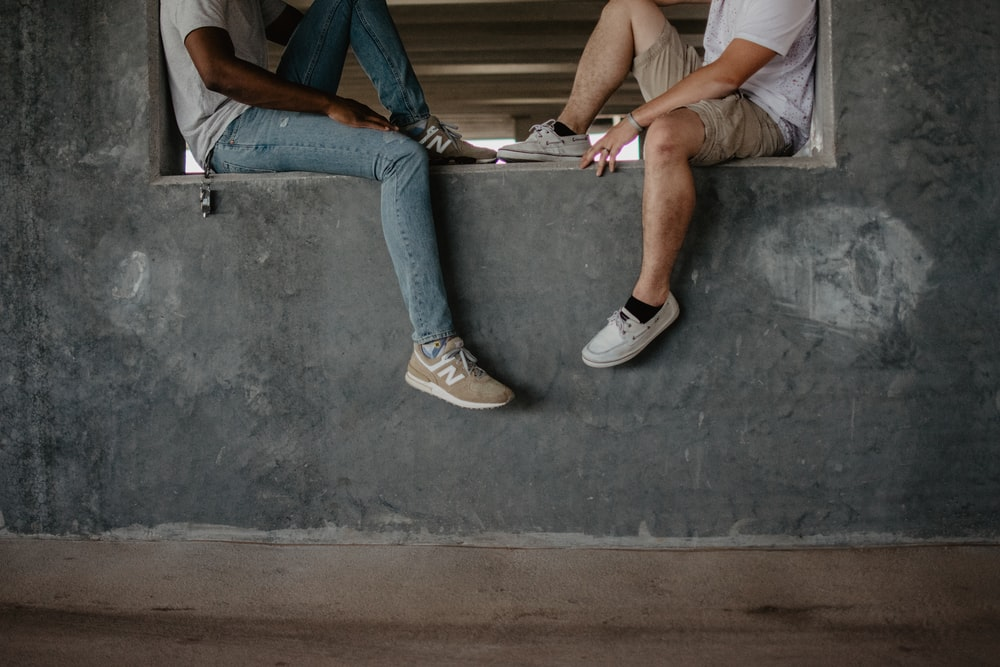 two men sitting on window