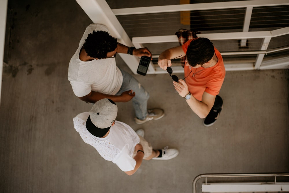 three men standing beside metal rail