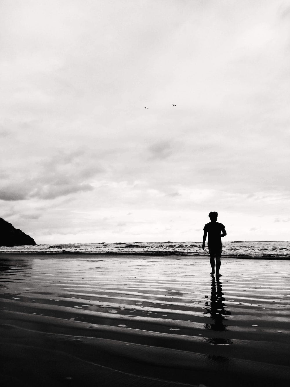 grayscale photo of man on shore
