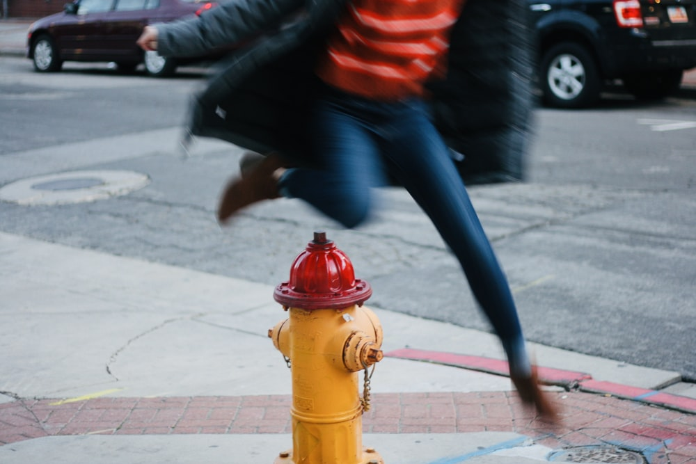 time lapse photography of person jumping over a water hydrant