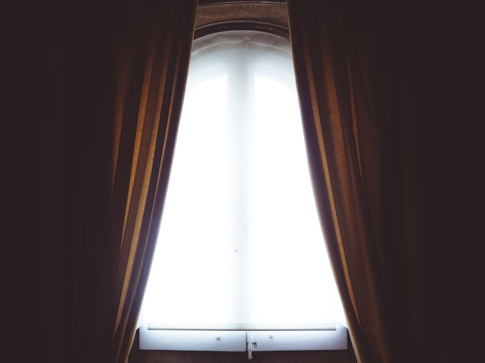 clear glass window and brown curtain panel